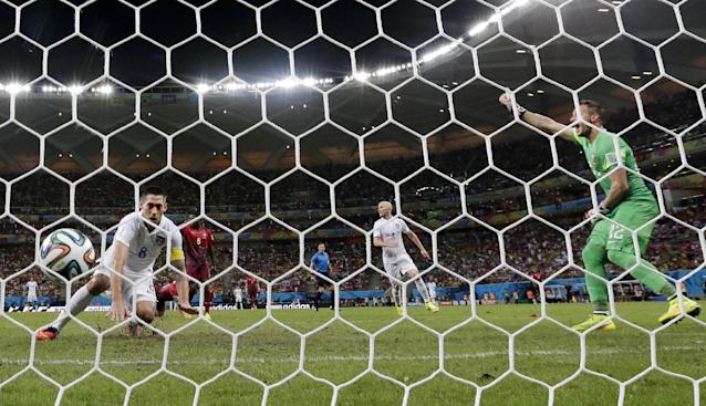 United States' Clint Dempsey, left, scores his side's second goal during the group G World Cup soccer match between the USA and Portugal at the Arena da Amazonia in Manaus, Brazil, Sunday, June 22, 2014. (AP Photo/Julio Cortez)