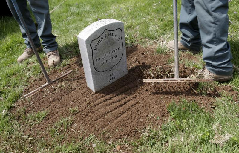 In this May 3, 2011 photo, employees of Green-Wood Cemetery install a headstone over the previously unmarked grave of a Civil War veteran at Green-Wood Cemetery in the Brooklyn borough of New York. A project at the cemetery hopes to identify the nearly 8,000 Civil War soldiers buried beneath the green expanse in the New York City outer borough. (AP Photo/Seth Wenig)