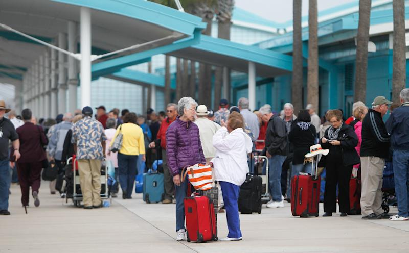 Passengers wait for their mode of transportation after getting off the Caribbean Princess cruise ship, Friday, Jan. 31, 2014, in La Porte, Texas. The ship returned to port early on Friday due to a dense fog advisory and not because people were vomiting and had diarrhea, a Princess Cruises spokeswoman said Friday. But passengers said the crew announced on the second day of the cruise that people were sick, apparently with highly contagious norovirus, and that extra precautions were being taken to ensure it didn't spread. (AP Photo/Houston Chronicle, Cody Duty)