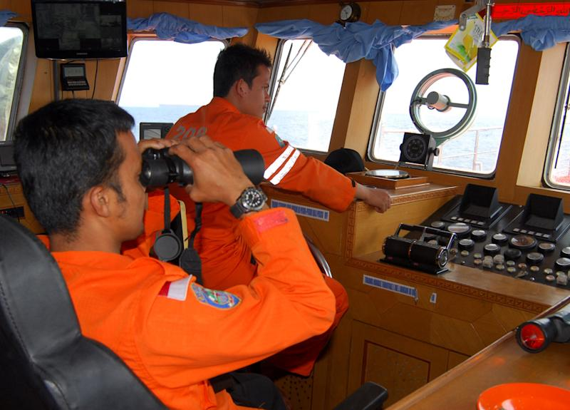 A member of Indonesian National Search And Rescue Agency (BASARNAS) uses a binocular to scan the horizon during a search operation for the missing Malaysia Airlines Boeing 777 conducted on the waters of the Strait of Malacca off Sumatra island, Indonesia, Wednesday, March 12, 2014. Malaysia asked India to join the expanding search for the missing Boeing 777 near the Andaman Sea, far to the northwest of its last reported position and a further sign Wednesday that authorities have no idea where the plane might be more than four days after it vanished. (AP Photo/Heri Juanda)