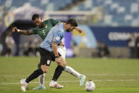 Uruguay's Luis Suarez, front, fights for the ball with Bolivia's Adrian Jusino during a Copa America soccer match at Arena Pantanal in Cuiaba, Brazil, Thursday, June 24, 2021. (AP Photo/Andre Penner)