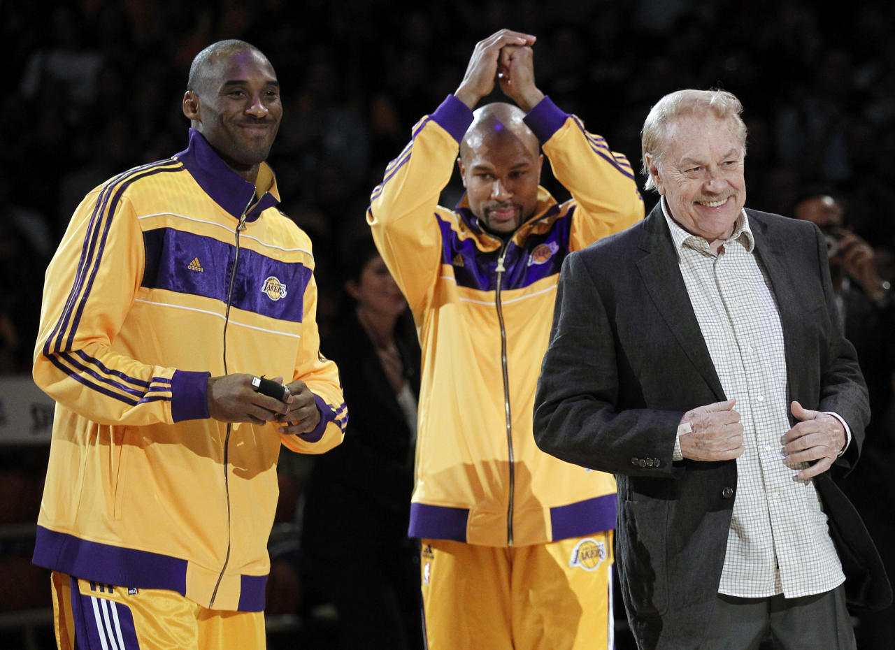Los Angeles Laker owner Jerry Buss, right, walks out onto the court during the NBA championship ring ceremony as Kobe Bryant, left, and Derek Fisher look on before a basketball game against the Houston Rockets in Los Angeles, Tuesday, Oct. 26, 2010.