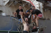 Civilians help to evacuate an injured sailor from a ship which was docked near the explosion scene that hit the seaport of Beirut, Lebanon, Tuesday, Aug. 4, 2020. (AP Photo/Hussein Malla)