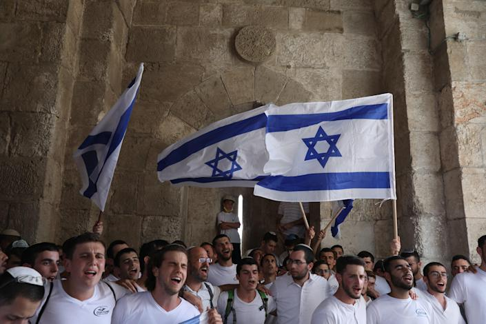 <p> Israelis march with national flags celebrating the Jerusalem liberation day at the Jaffa gate in the old city of Jerusalem, 10 May 2021. </p> (EPA)