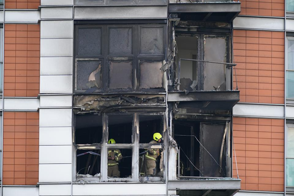 Firefighters inspect damage to a 19-storey tower block in New Providence Wharf in London, where the London Fire Brigade (LFB) was called to on Friday morning to reports of a fire and more than 100 firefighters are tackling a blaze that has ripped through the block, believed to be covered in cladding, in east London. Picture date: Friday May 7, 2021. See PA story FIRE CanaryWharf. Photo credit should read: Yui Mok/PA