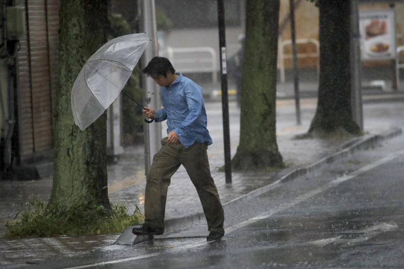 A man crosses the road in Hamamatsu, central Japan, Saturday, Oct. 12, 2019. A heavy downpour and strong winds pounded Tokyo and surrounding areas on Saturday as a powerful typhoon forecast as the worst in six decades approached landfall, with streets and train stations deserted and shops shuttered. (AP Photo/Christophe Ena)
