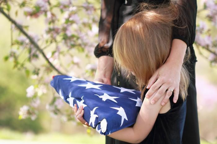 Little girl with mother's arm around her holding a folded American flag at a funeral.