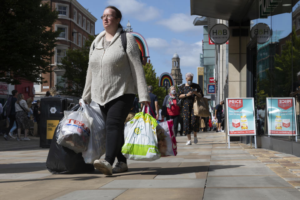 A woman carrying multiple bags of shopping up the city's main commercial street in Manchester, England. Photo: Daniel Harvey Gonzalez/In Pictures via Getty Images