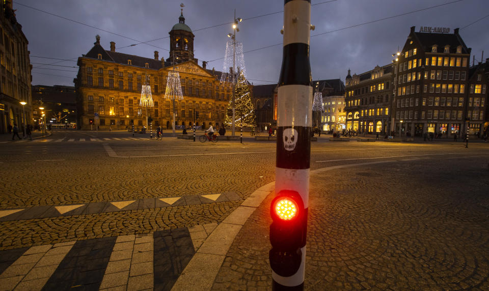 FILE- In this Tuesday Dec. 15, 2020, file photo, A skull is glued onto a traffic light on the near-empty Dam Square with the Royal Palace, seen center rear, in Amsterdam, Netherlands. The Dutch government said Wednesday, Jan. 20, 2021, that it wants to impose a curfew as part of beefed-up restrictions to rein in the spread of new more contagious variants of the coronavirus that already accounts for at least one in every 10 Dutch infections.(AP Photo/Peter Dejong, File)