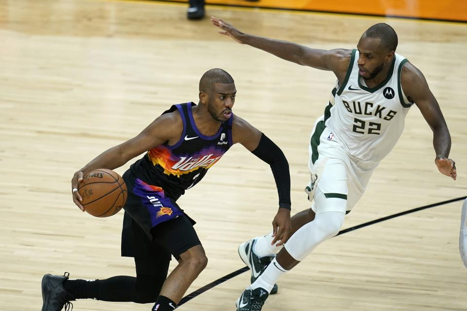 Phoenix Suns guard Chris Paul, left, dribbles the ball against Milwaukee Bucks forward Khris Middleton (22) during the second half of Game 1 of basketball's NBA Finals, Tuesday, July 6, 2021, in Phoenix. (AP Photo/Ross D. Franklin)