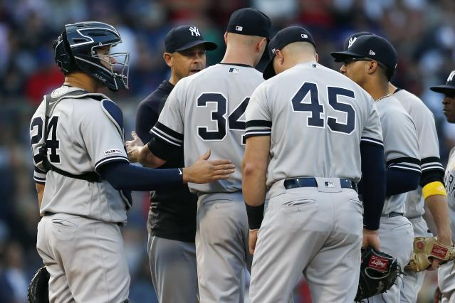 New York Yankees manager Aaron Boone, second from left, relieves J.A. Happ (34) during the seventh inning of a baseball game against the Boston Red Sox in Boston, Saturday, Sept. 7, 2019. (AP Photo/Michael Dwyer)