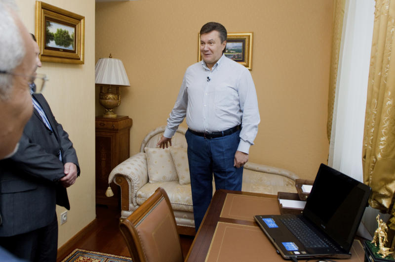 In this photo taken Friday, June 24, 2011, during a tour organized by the Ukrainian Presidential press-service, President Viktor Yanukovych, right, talks to journalists he invited to see his official residence called Mezhygirya, outside Kiev, Ukraine. When Ukraine's president opened up his home to TV cameras, he presented a cozy place with a small office just big enough for his grandchildren to play in. But his critics point to strong evidence he actually lives in very different digs: a luxurious, marble-columned mansion with a golf course, a helipad and even an ostrich enclosure. (AP Photo/Mykhailo Markiv, Presidential Press Service)