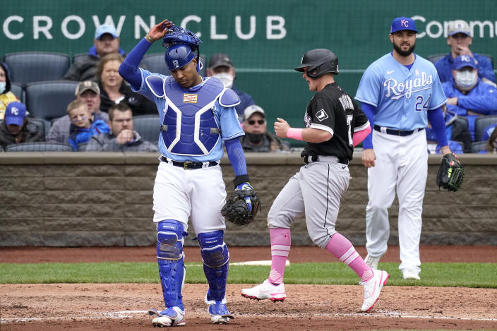 Chicago White Sox's Andrew Vaughn runs between Kansas City Royals catcher Salvador Perez and pitcher Jakob Junis (24) to score on a single by Leury Garcia during the sixth inning of a baseball game Sunday, May 9, 2021, in Kansas City, Mo. (AP Photo/Charlie Riedel)