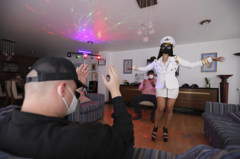 A woman wearing a protective face mask amid the new coronavirus pandemic, dances in a client's home in Mexico City, Saturday, Aug. 8, 2020. The pandemic has forced business to adapt to a new normality and the adult entertainment industry is no exception. After three months of inactivity, Mi Ultimo Beso relaunched its table-dance-at-home service observing health measures. (AP Photo/Eduardo Verdugo)