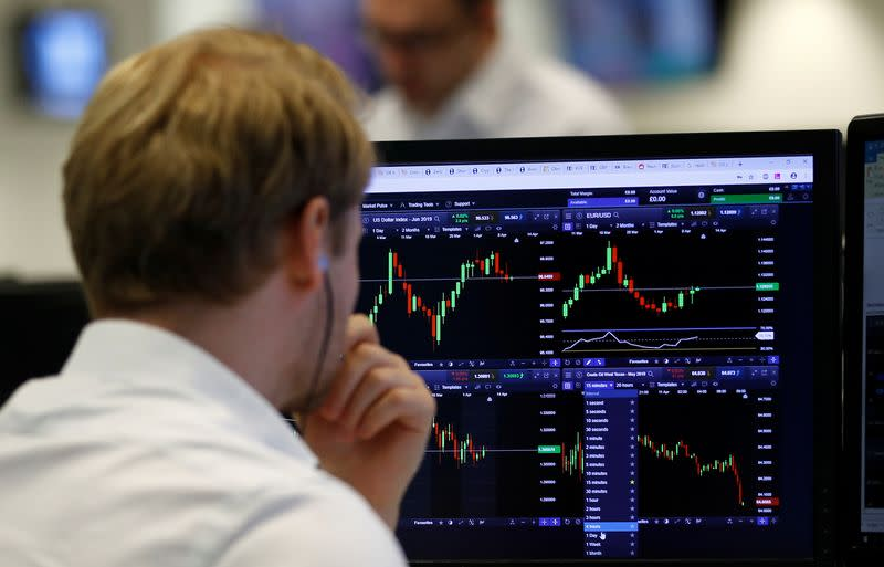 FILE PHOTO: A financial trader works at their desk at CMC Markets in the City of London