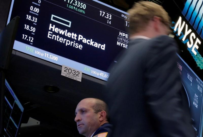 FILE PHOTO: A trader passes by the post where Hewlett Packard Enterprise Co., is traded on the floor of the New York Stock Exchange