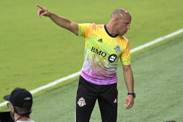 Toronto FC head coach Chris Armas talks to his staff in front of the bench during the first half of an MLS soccer match against FC Cincinnati, Saturday, June 26, 2021, in Orlando, Fla. (AP Photo/Phelan M. Ebenhack)