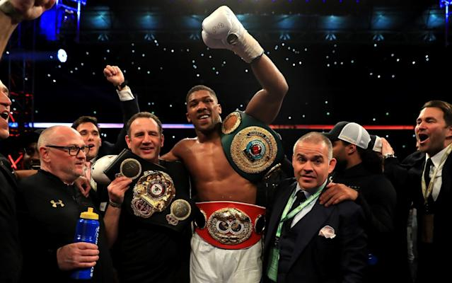 Anthony Joshua celebrates with his team after retaining his IBF heavyweight title and adding the WBA and IBO belts to his collection - Getty Images Europe