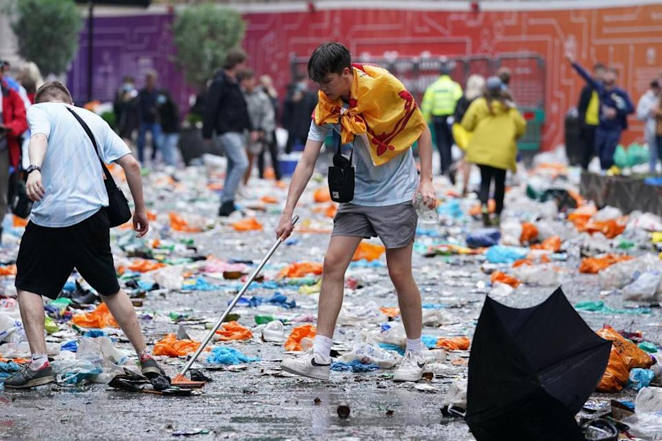 Scotland fans clean up litter in Leicester Square, London, before the Euro 2020 match between England and Scotland.