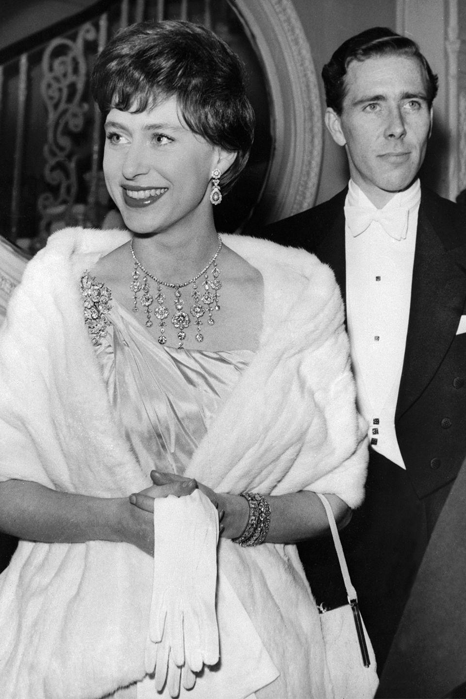 <p>Here's Princess Margaret at the Opera House in London wearing an elegant gown and white and fur wrap. This is the same year she married Anthony Armstrong-Jones (pictured behind her). </p>