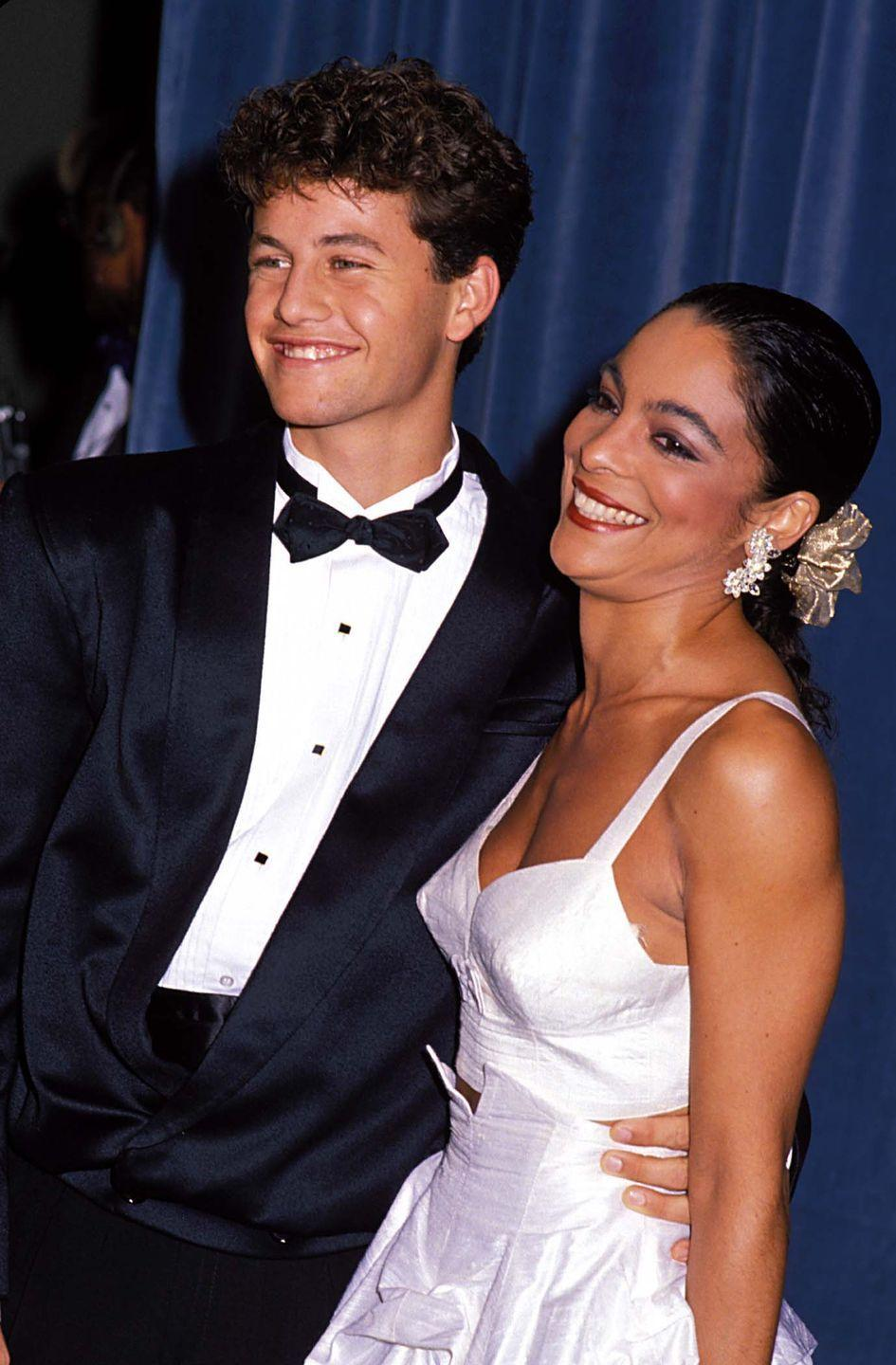 """<p>The young stars of """"A Different World"""" arrive together—her in a two-piece white bustier and ruffled skirt, him in a classic tux.</p>"""
