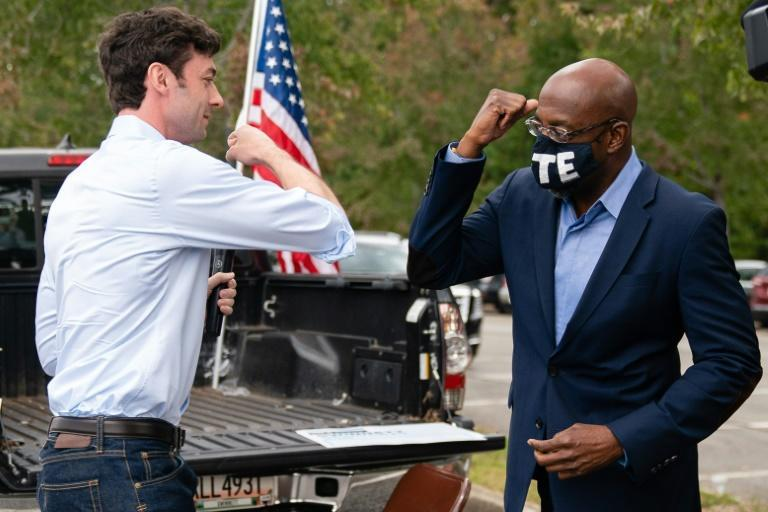 Democratic Senate candidates Jon Ossoff (L) and Rev. Raphael Warnock (R) bump elbows at a rally in Duluth, Georgia