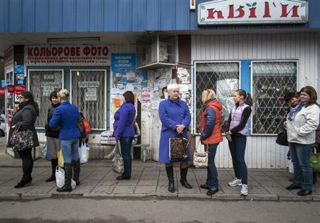 People wait for a bus at a bus station in the small Ukrainian town Pustomyty