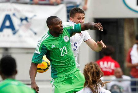 Nigeria forward Shola Ameobi (23) and United States defender Matt Besler (5) miss the header during the first half at EverBank Field. Mandatory Credit: Kim Klement-USA TODAY Sports