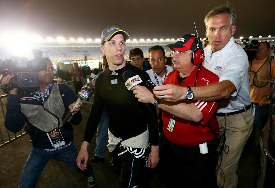 Brad Keselowski (second from left)speaks with the media after the NASCAR Sprint Cup Series Bank of America 500 at Charlotte Motor Speedway on October 11, 2014 in Charlotte, North Carolina (AFP Photo/Streeter Lecka)
