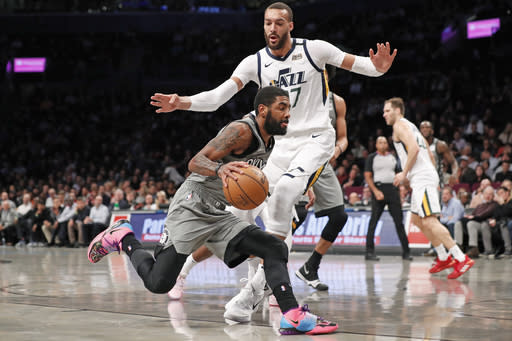 Brooklyn Nets guard Kyrie Irving (11) drives around Utah Jazz center Rudy Gobert (27) during the first quarter of an NBA basketball game Tuesday, Jan. 14, 2020, in New York. (AP Photo/Kathy Willens)