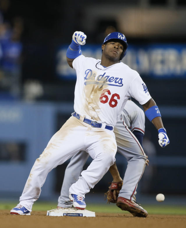 Los Angeles Dodgers' Yasiel Puig pumps his fist after hitting a double against the Atlanta Braves in the eighth inning of Game 4 in the National League baseball division series Monday, Oct. 7, 2013, in Los Angeles. Puig went on to score on a two-run home run by Juan Uribe and the Dodgers won 4-3, advancing to the NL championship series.. (AP Photo/Danny Moloshok)