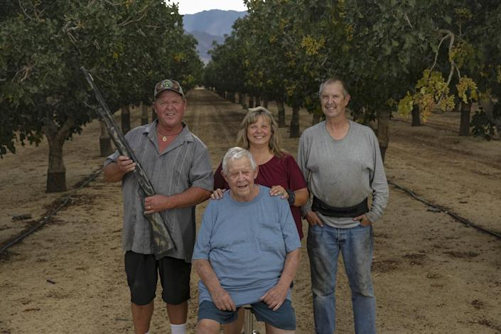 Family members pose in an orchard
