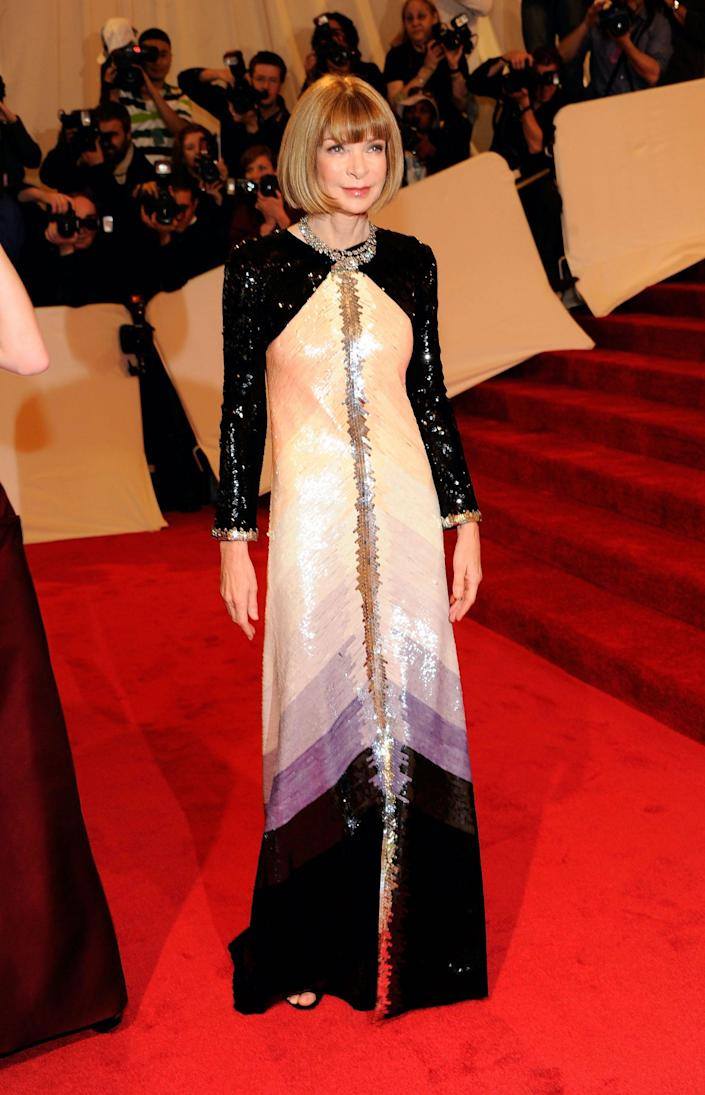 Anna Wintour wears a black and ombre long sleeve dress on a red carpet.