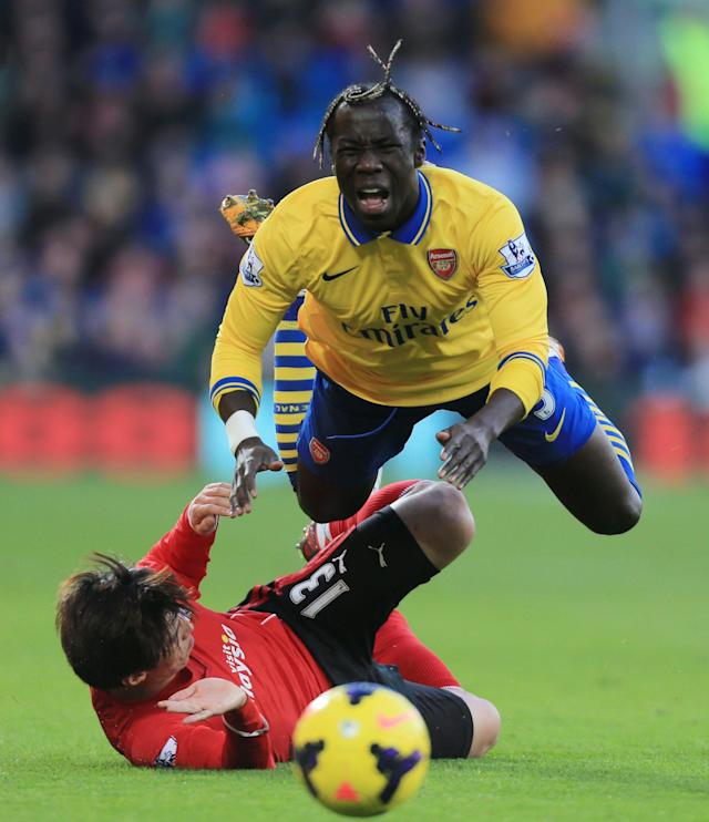 Arsenal's Bacary Sagna is tackled by Cardiif City's Kim Bo-Kyung, below, during their English Premier League soccer match at Cardiff City Stadium, Cardiff, Wales, Saturday, Nov. 30, 2013. (AP Photo/Nick Potts, PA Wire)