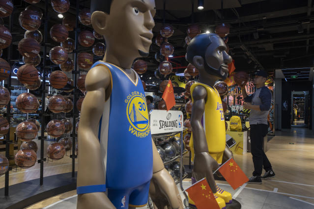 "In this Friday, Oct. 11, 2019, photo, a shopper reach holds a basketball near statues of NBA players Stephen Curry of the Golden State Warriors, left, and Lebron James of the Los Angeles Lakers holding Chinese flags in the entrance of an NBA merchandise store Beijing. When Houston Rockets' general manager Daryl Morey tweeted last week in support of anti-government protests in Hong Kong, everything changed for NBA fans in China. A new chant flooded Chinese sports forums: ""I can live without basketball, but I can't live without my motherland."" (AP Photo/Ng Han Guan)"