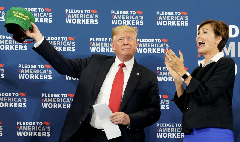 "U.S. President Donald Trump holds up a ""Make Our Farmers Great Again"" cap next to Iowa Governor Kim Reynolds in Peosta, Iowa, U.S., July 26, 2018. (Photo: REUTERS/Joshua Roberts)"