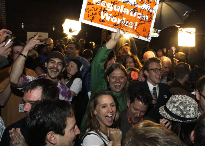 People attending an Amendment 64 watch party in a bar celebrate after a local television station announced the marijuana amendment's passage, in Denver, Colo., Tuesday, Nov. 6, 2012. The amendment would make it legal in Colorado for individuals to possess and for businesses to sell marijuana for recreational use. (AP Photo/Brennan Linsley)