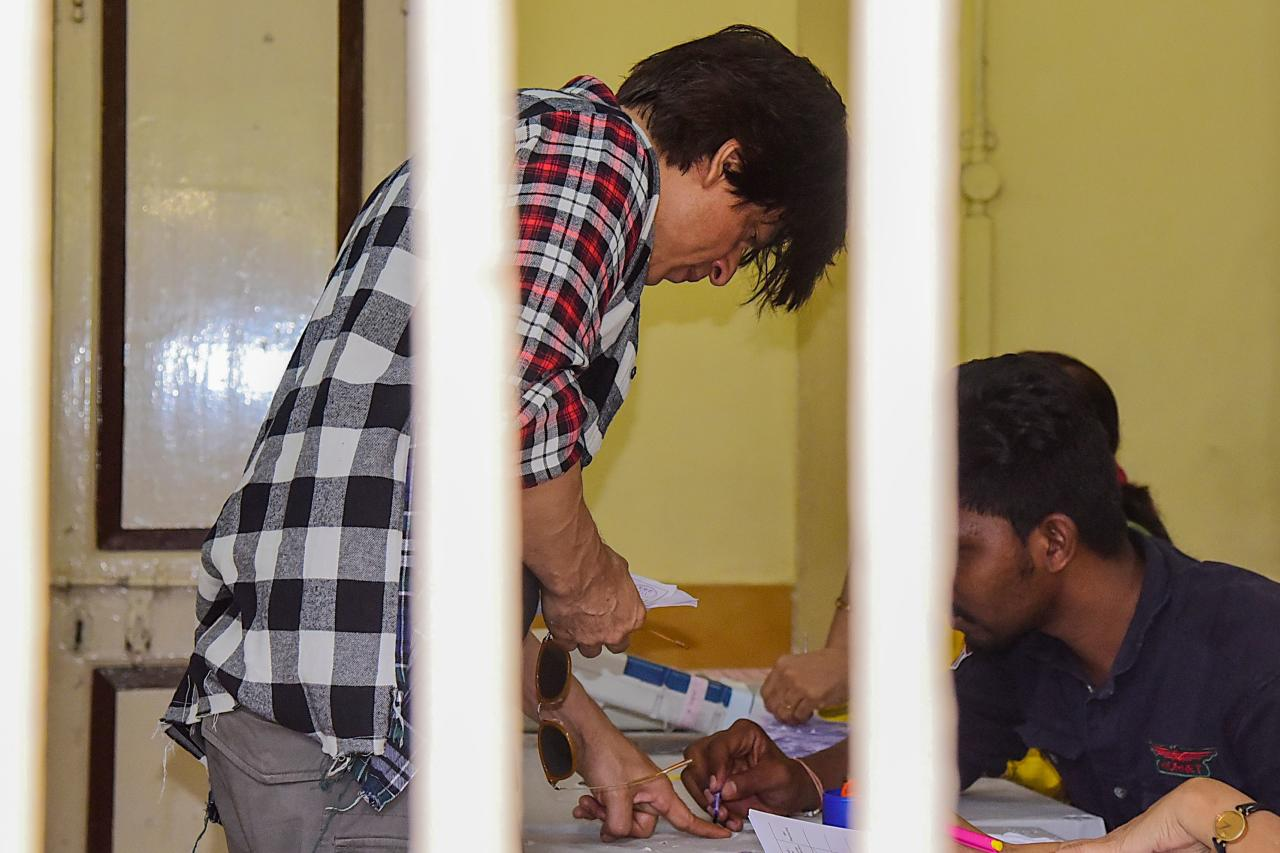 Bollywood actor Shah Rukh Khan (L) interacts with officials as he casts his vote at a polling station during the state assembly election in Mumbai on October 21, 2019. (Photo by Sujit Jaiswal / AFP) (Photo by SUJIT JAISWAL/AFP via Getty Images)