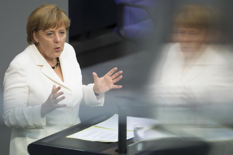 German Chancellor Angela Merkel addresses lawmakers on the decisions of the EU summit at the parliament Bundestag in Berlin, Friday, June 29, 2012. Chancellor Merkel faces a vote on the eurozone's new permanent rescue fund and the EU's fiscal co-pact. Merkel is reflected in the windows of a visitors balcony at the plenary hall. (AP Photo/Markus Schreiber)