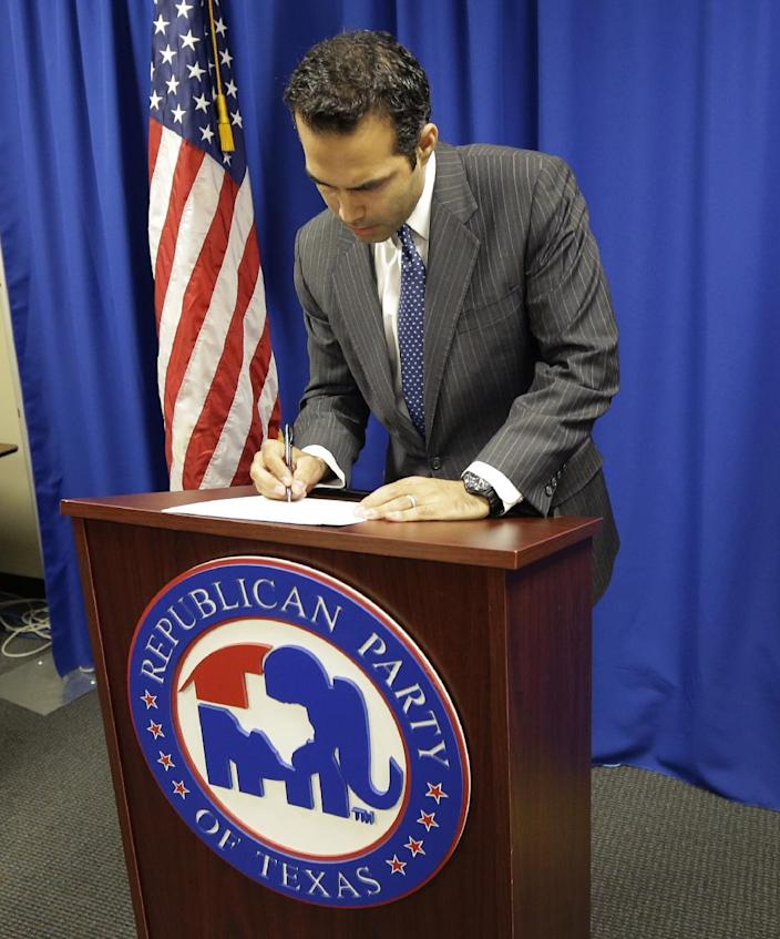 """File - In this Nov. 19, 2013 file photo, George P. Bush, the grandson of one former president and nephew of another, signs papers at the Republican Party of Texas headquarters in Austin, Texas, where he formally filed to run for Texas land commissioner. Rather than campaigning on the mainstream Republicanism embodied by the family name, Bush says he's """"a movement conservative"""" more in line with the tea party. (AP Photo/Eric Gay, File)"""
