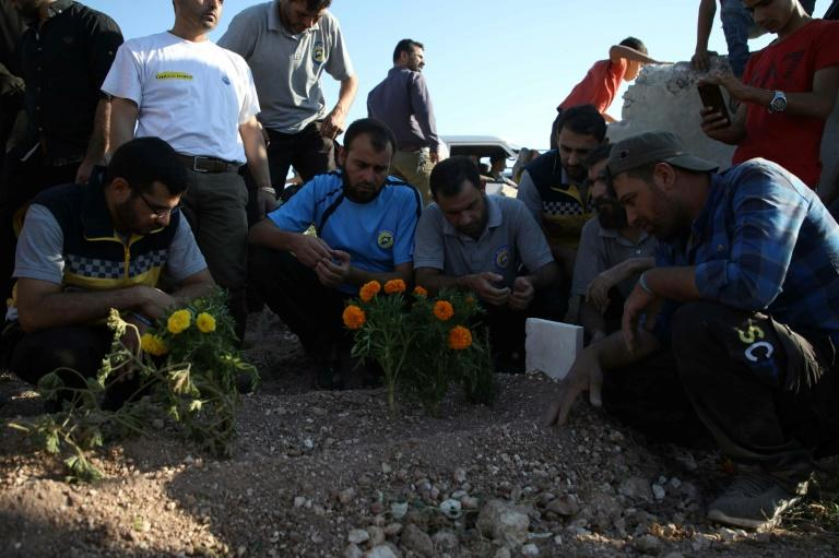Mourners pray at the grave of Anas al-Dyab, who rescuers say was killed Sunday in Russian air strikes (AFP Photo/Aaref WATAD)