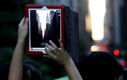 A woman takes a photo with an iPad as people wait for the sun to set through the middle of the buildings on 42nd Street in New York's Manhattan borough during a phenomenon known as Manhattanhenge, Wednesday, July 11, 2012. Manhattanhenge, sometimes referred to as the Manhattan Solstice, happens when the setting sun aligns with the east-to-west streets of the main street grid. The term references Stonehenge, at which the sun aligns with the stones on the solstices in England. (AP Photo/Julio Cortez)