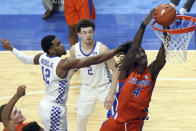 Florida's Anthony Duruji (4) dunks near Kentucky's Keion Brooks Jr. (12) and Devin Askew (2) during the first half of an NCAA college basketball game in Lexington, Ky., Saturday, Feb. 27, 2021. (AP Photo/James Crisp)
