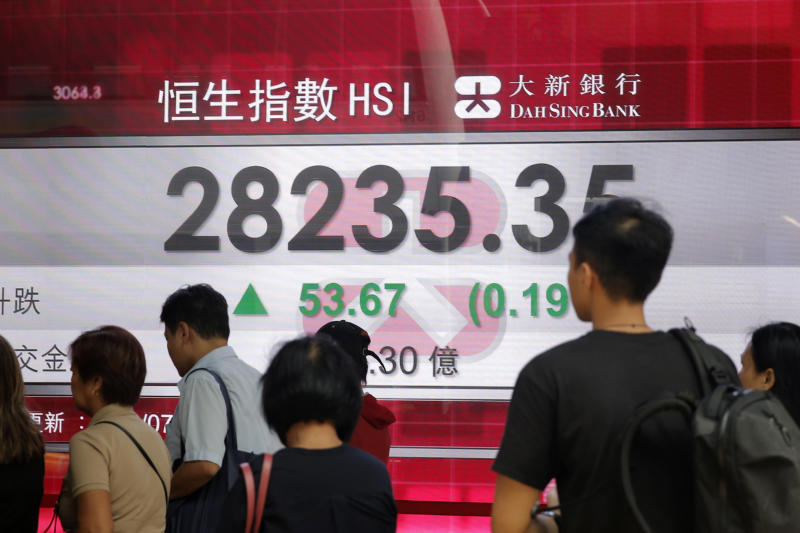 People walk past an electronic board showing Hong Kong share index outside a bank in Hong Kong, Wednesday, July 18, 2018. Asian markets climbed higher on Wednesday as a sweep of positive news from Wall Street and beyond boosted confidence in the U.S. economy. (AP Photo/Kin Cheung)