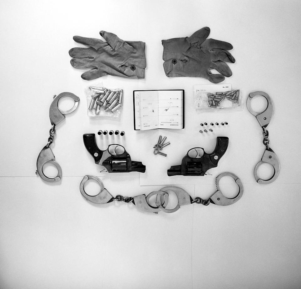 A photo of various articles found by police in the possession of Ian Ball, 26, including handcuffs, two pairs of which are locked together to provide leg shackles, keys for the handcuffs, gloves worn by Ball during the incident, six spent rounds, three live rounds and 39 spares for the .22 gun and a .38 Astra with five spent rounds and 19 spares. The diary belonged to shot PC Michael Hills, with the bullet that pierced it still lodged in his liver.
