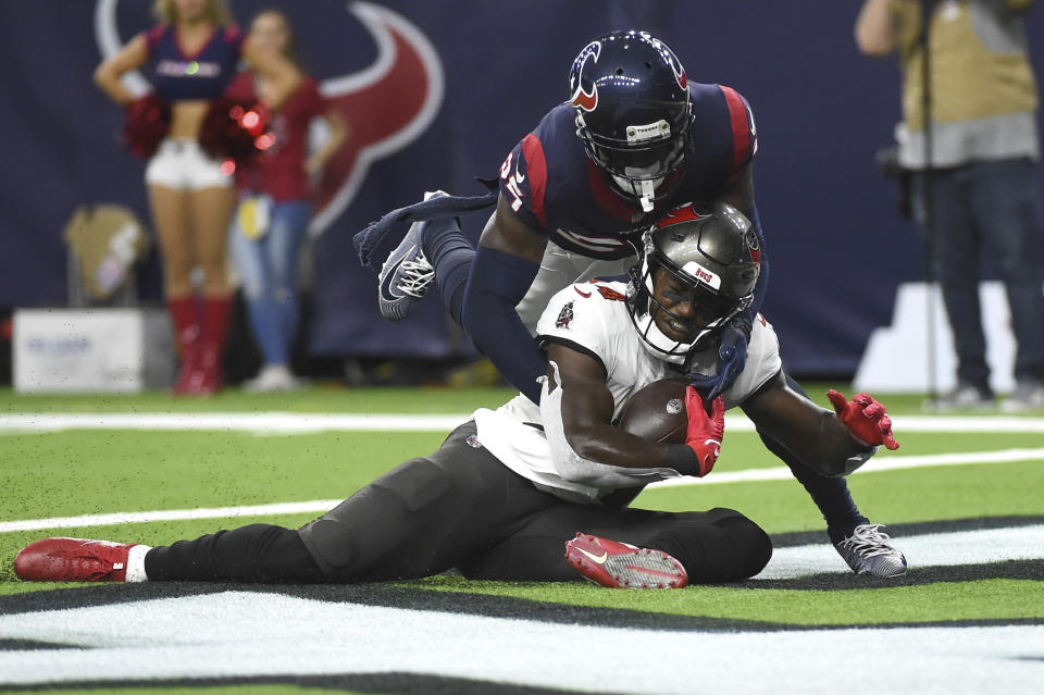 Tampa Bay Buccaneers wide receiver Chris Godwin (14) is tackled by Houston Texans' Desmond King II (25) after making a catch and run for a touchdown during the first half of an NFL preseason football game Saturday, Aug. 28, 2021, in Houston. (AP Photo/Eric Christian Smith)