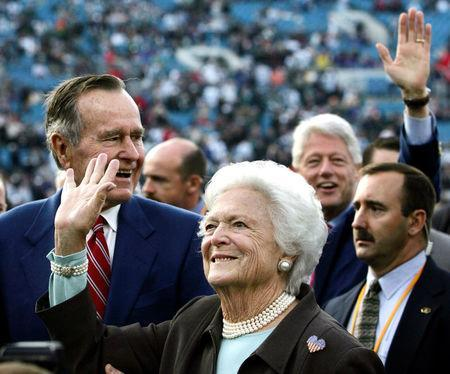 Former first lady Barbara Bush (C) waves to fans as she walks on the field with former U.S. presidents George Bush (L) and Bill Clinton (2nd R) before Super Bowl XXXIX in Jacksonville February 6, 2005. REUTERS/Marc Serota/Files