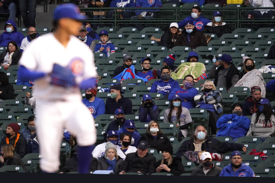 Fans are bundled up in the cold weather as they watch a baseball game between the Los Angeles Dodgers and the Chicago Cubs in Chicago, Wednesday, May 5, 2021. (AP Photo/Nam Y. Huh)