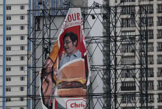 A Filipino worker brings down a billboard sign in Manila, Philippines as Typhoon Utor approaches on Sunday, Aug. 11, 2013. More than 3,000 passengers were stranded on piers in the northeastern Philippines Sunday, as the strong typhoon approaches and prompted authorities to suspend ferry services and warn people to brace for possible flash floods and landslides.(AP Photo/Aaron Favila)