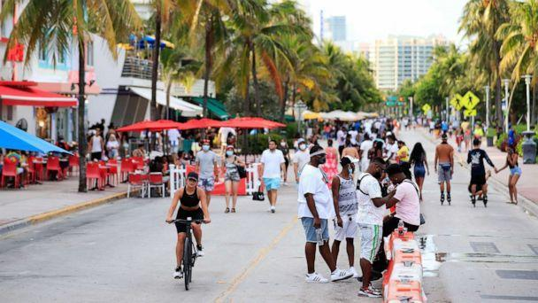 PHOTO: A woman rides her bike past pedestrians on Ocean Drive on July 03, 2020, in the South Beach neighborhood of Miami Beach, Fla. (Cliff Hawkins/Getty Images)